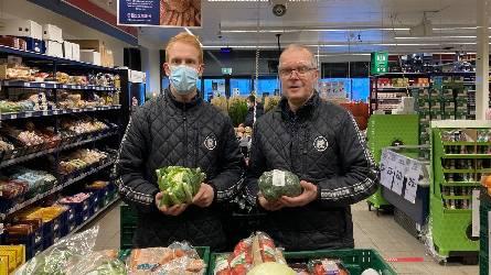 Store staff holding veg
